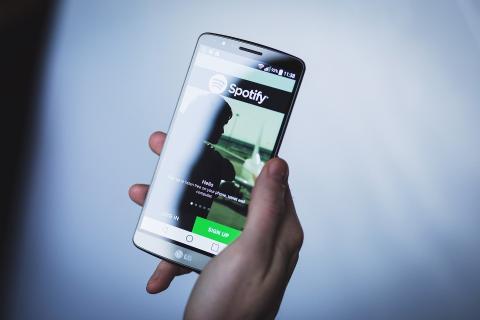 Una persona sujeta un teléfono móvil con la aplicación de Spotify abierta.