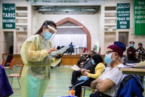 Sanitaria lee informe de un paciente antes de vacunarle contra el COVID-19.