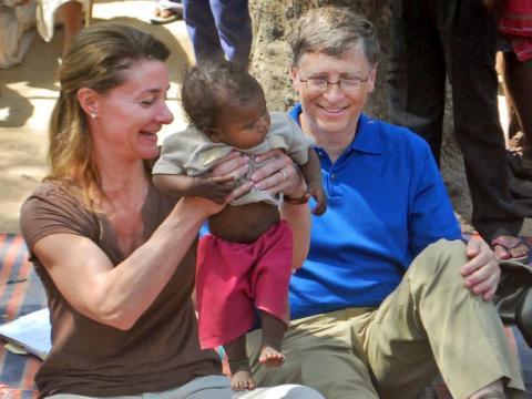 Bill Gates y su mujer Melinda Gates atienden a un niño mientras se reúnen con miembros de la comunidad Mushar en Jamsot Village cerca de Patna, India.