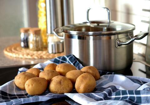 Una cazuela y unas patatas en la cocina.