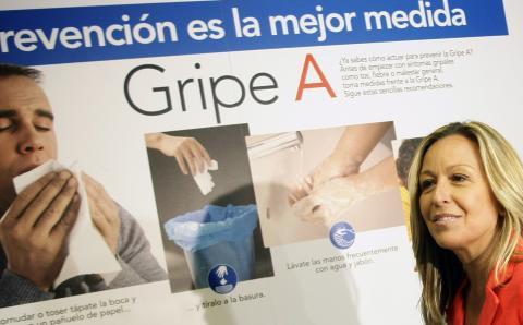 Trinidad Jiménez, cuando era ministra de Sanidad, delante de un cartel sobre la gripe A.