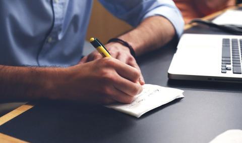 Un hombre escribe en un papel.
