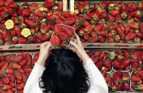mujer comprando fresas