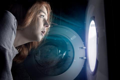 Una mujer mira a oscuras el interior de la lavadora.
