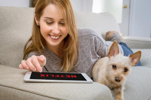 Una mujer con su perro abre Netflix en una tablet.