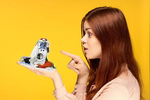 Una mujer sostiene una lavadora en miniatura.
