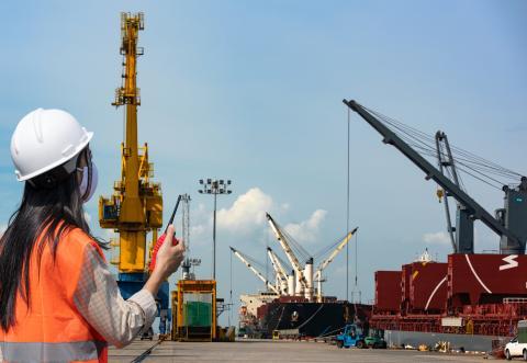 Una mujer supervisa la carga de un barco en un puerto.