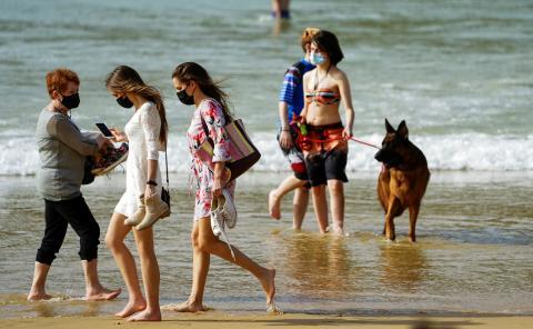 Mujeres con mascarilla en la playa