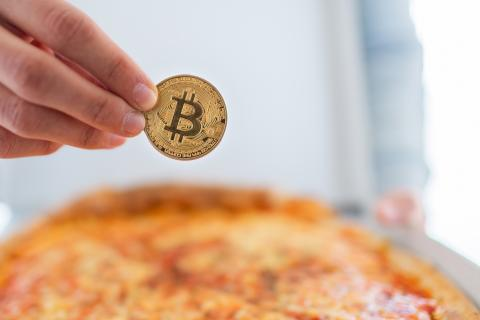 Una persona paga una pizza con bitcoin.