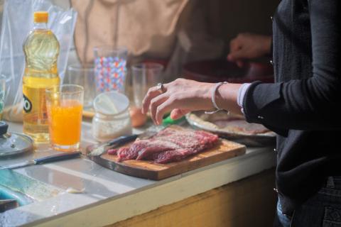 Una persona prepara un trozo de carne para ser cocinado.