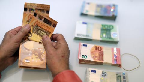 Un tendero cuenta billetes de euro en su tienda en Niza (Francia)