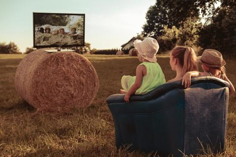 Tres niñas ven la televisión en el campo.