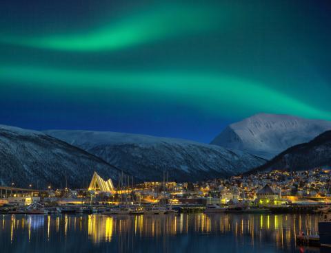 La ciudad de Tromso por la noche iluminada por una aurora boreal.