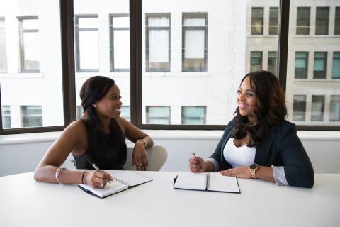 Dos mujeres hablan en una entrevista de trabajo.