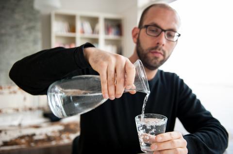 Un hombre se echa agua en un vaso