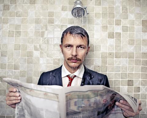 Un hombre lee el periódico vestido bajo la ducha.