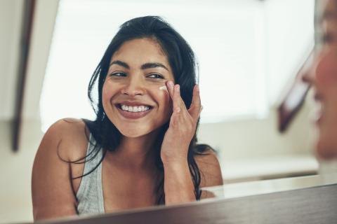 mujer dándose crema en la cara, arrugas