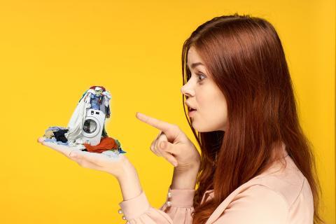 Una mujer con una lavadora en miniatura en la mano.