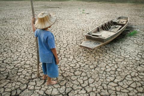 Niño junto a una barca en un río seco.