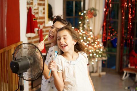 Un niño y una niña juegan delante del ventilador.