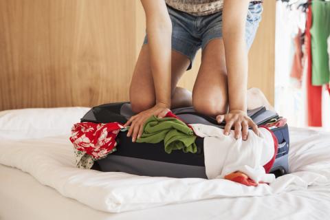 Una persona aprieta la maleta para intentar cerrarla.