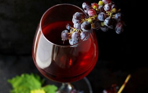 Un racimo de uvas sobre una copa de vino.