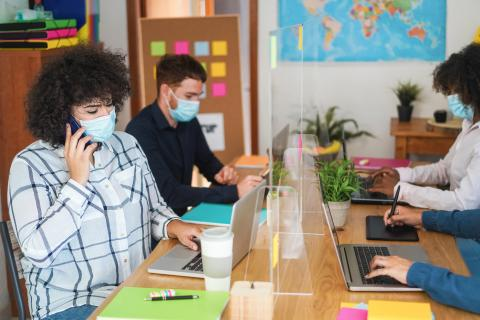 Trabajadores de oficina hablando por teléfono.