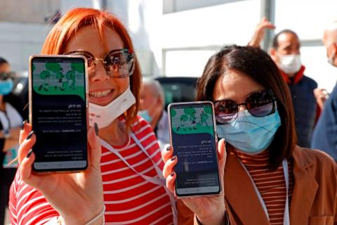 """Israelis show off their """"green passes"""" as they arrive for a concert for vaccinated seniors at Bloomfield Stadium in Tel Aviv on March 5, 2021."""