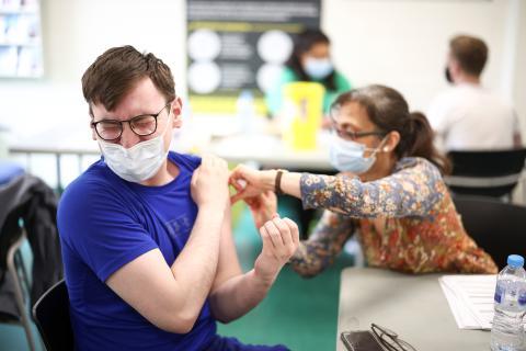 Vacunan a un hombre con la candidata de Pfizer y BioNTech.