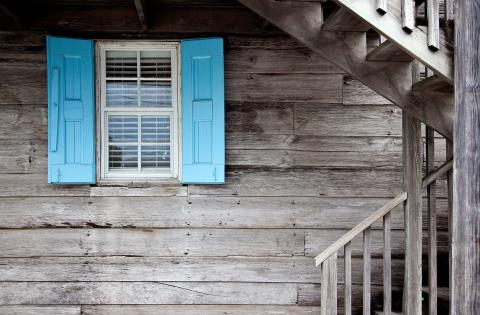 Una ventana antigua en una casa de madera.
