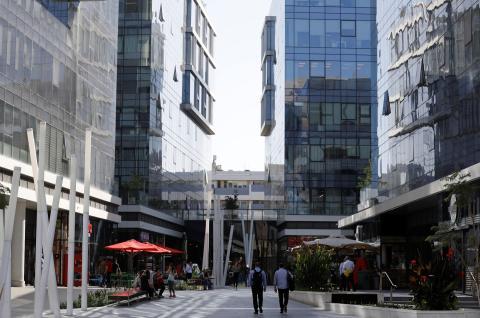 Dos personas caminan entre las sedes de varias empresas tecnológicas en Tel Aviv