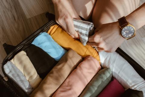 Enrollar la ropa en la maleta.