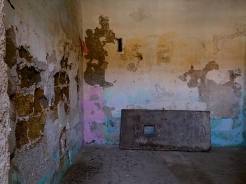 Imagen de una celda, que tiene pintura descascarada de sus paredes.