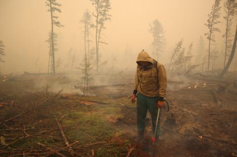 Un especialista del servicio local de protección forestal trabaja para extinguir un incendio forestal cerca del pueblo de Magaras en la región de Yakutia (Rusia) el 17 de julio de 2021.
