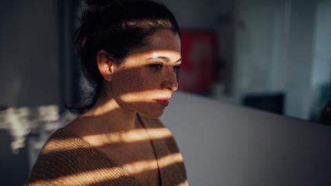 Una mujer a oscuras en casa con las persianas bajadas