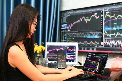 Una mujer trabaja con varios ordenadores y pantallas.