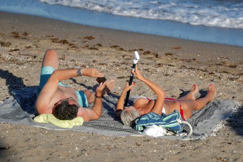 Una pareja toma el sol en la arena de la playa.