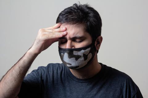 Una persona con mascarilla se agarra la cabeza.