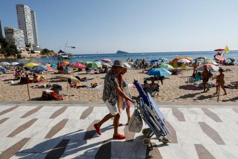 Personas andando por la playa de vacaciones.