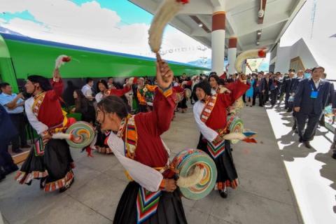 Los residentes locales bailan junto al primer tren bala Fuxing en la estación de tren de Lhasa en el ferrocarril de Lhasa-Nyingchi.