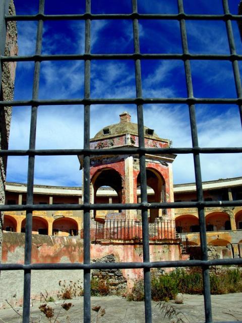Vista a través de una ventana de rejilla hacia el patio de la prisión.