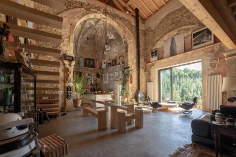 Las paredes texturizadas de la casa se equilibran con el suelo de cemento pulido y los muebles de corte limpio.