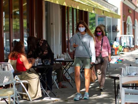 Gente andando por la calle con mascarillas.
