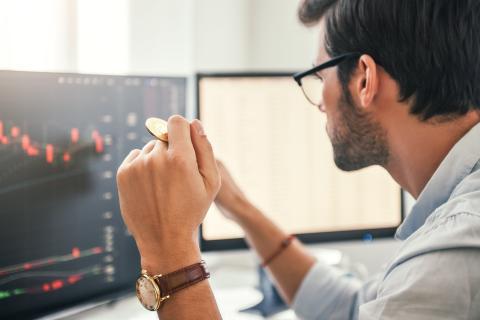 Un joven trabaja sosteniendo un bitcoin