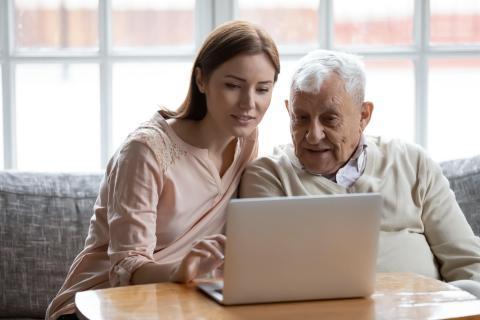 Una mujer ayudando a su padre con el ordenador