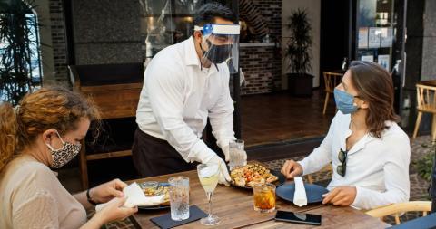 Dos mujeres comen en un restaurante al aire libre.