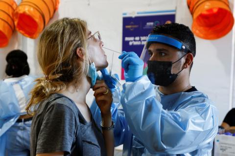 Un sanitario hace una PCR a una mujer para detectar COVID-19.