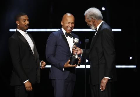 Bryan Stevenson, en el centro, recoge un premio de manos de Morgan Freeman, acompañado por Michael B. Jordan.