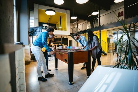 Compañeros de trabajo juegan en una oficina con un futbolín