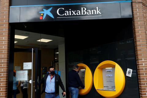 Un hombre saca dinero de un cajero de CaixaBank